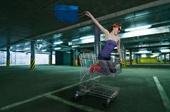 Red girl riding shopping cart at Stock Photography