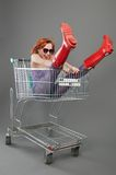 Red girl riding on a shopping cart Stock Photos