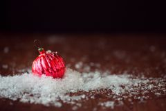 Red glass ball. Christmas toy. In a pile of snow, wood textured background, rustic style Royalty Free Stock Photos