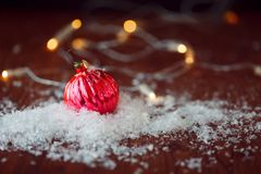 Red glass ball. Christmas toy. In a pile of snow, wood textured background, rustic style Royalty Free Stock Image