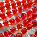 Red glass beads on bright background. royalty free stock images