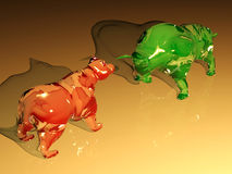 Red glass bear figure confronts green glass bull figure Stock Image