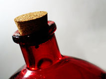 Red Glass Bottle. A high contrast macro shot of a corked red bottle Stock Photo