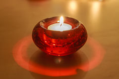 Red Glass Candle Holder with White Candle Stock Image