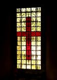 Red glass crucifix with black border. Red stained glass crucifix in glass panel with black border Royalty Free Stock Photography
