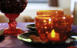 Red glass cup of the table. Fire of the candle in the red glass cup of the table of the room Royalty Free Stock Image