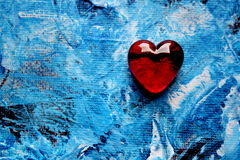Red Glass Heart on Blue Painted background Stock Photos