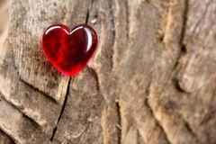 Red Glass Heart on soft focus timber background Royalty Free Stock Photos
