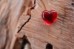 Red Glass Heart with soft focus wood background Royalty Free Stock Image