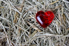 Red Glass Heart on straw background Stock Photo