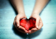 Red glass heart in woman hands Stock Photo