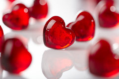 Red glass hearts. Red glass heart shape against others on white background Stock Image