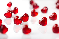 Red glass hearts background. Many red glass heart shapes on white background Stock Photography