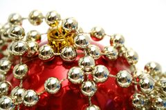 Red glass sphere and celebratory beads on a white Royalty Free Stock Photography