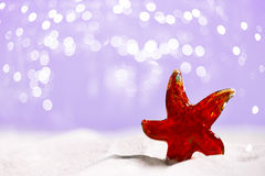 Red Glass star fish on beach sand Royalty Free Stock Photography