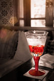 Red Glass Of Water On The Table With Sun Light : Selective Focus Royalty Free Stock Photos