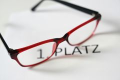 Red glasses above the german text 1 Platz, that means first place, competition jury concept. Selected focus, narrow depth of field royalty free stock image