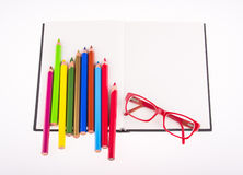 Red glasses and color pencils placed on notebook Stock Photos