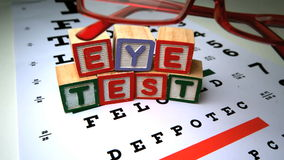Red glasses falling next to blocks spelling out eye test. In slow motion stock footage