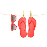 Red glasses and flip flops hanging on rope with clothespins, isolated on white, summer background Royalty Free Stock Images