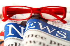 Red glasses on newspaper Stock Photos