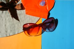 Sun protective glasses, hat on blue and orange background royalty free stock photos