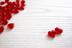 Red glassy hearts. On a white wooden background stock photos
