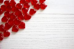 Red glassy hearts. On a white wooden background royalty free stock photo