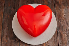 Red glaze mousse cake, heart shape form on wooden background Stock Images