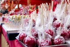 Red glazed candy apples wrapped in cellophane on display stock photography