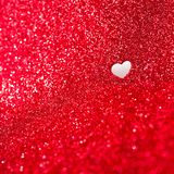 Valentines day background with red glitter. Red glitter background with one heart shaped cut out hole Royalty Free Stock Photography