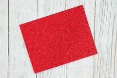 Red glitter blank greeting card on weathered whitewash textured wood background stock photography