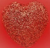A red glitter heart. With red background color Royalty Free Stock Photos