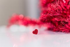 Valentinesday conceptual image. Red glitter heart banner with red tinsel unfocused background Stock Image