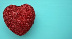 A red glitter heart. On a blue background Stock Image