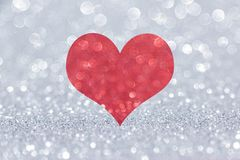 Red glitter heart on silver background stock photo