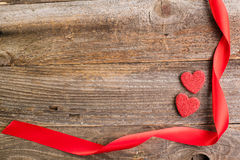 Red glitter hearts with red satin ribbon on reclaimed wood, vale Stock Photography