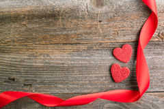 Red glitter hearts with red satin ribbon on reclaimed wood, vale Royalty Free Stock Image
