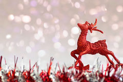 Red glitter reindeer ornament on white snow with abstract backgr Stock Photos