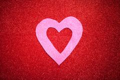 Red glittery background with pink heart, Valentine`s Day, texture abstract background, suitable for ads, insert text, romantic. Red glittery background with pink stock photography