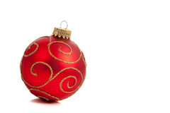 A red, glittery Christmas ornament on white. A red with gold glitter Christmas ornament on a white background stock photography