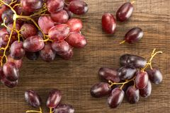 Fresh raw red wine grapes on brown wood. Red globe grape berries table top isolated on brown wood background fresh dark pink Stock Image