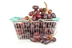 Fresh raw red wine grapes isolated on white. Red globe grape cluster in a shopping basket isolated on white background shiny dark pink berries Stock Images