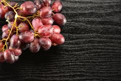 Fresh raw red wine grapes on black wood. Red globe grape cluster table top isolated on black wood background dark pink berries Royalty Free Stock Photo