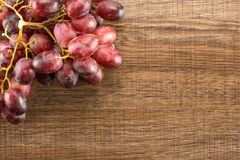 Fresh raw red wine grapes on brown wood. Red globe grape cluster table top isolated on brown wood background dark pink berries Stock Photography