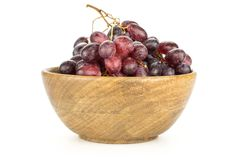 Fresh raw red wine grapes isolated on white. Red globe grape cluster in a wooden bowl isolated on white background fresh shiny dark pink berries Royalty Free Stock Photography