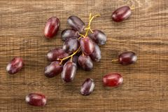 Fresh raw red wine grapes on brown wood. Red globe grape table top isolated on brown wood background dark pink berries Royalty Free Stock Image