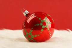 Red glossy christmas ball with green stars on white fur in front of red background Stock Photo