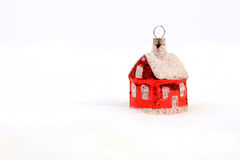 Red glossy Christmas decoration - little house standing on white fur background. 