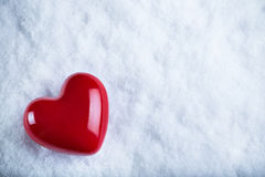 Red glossy heart on a frosty white snow background. Love and St. Valentine concept Stock Photography